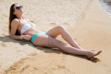Beautiful sexy girl lying on a sandy beach