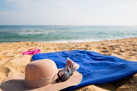 Photo for Hat, towel, sunglasses and slippers on a tropical beach. Concept of summer vacations. - Royalty Free Image