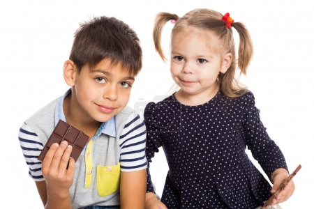 Cheerful brother and a younger sister with chocola...
