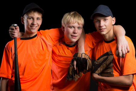 Foto de Cheerful young baseball players on a black background. Two of the boys twin brothers. - Imagen libre de derechos