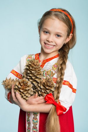 Girl in Russian folk costume holding pine cones