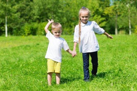 Photo pour Frère et sœur marchant dans le parc - image libre de droit