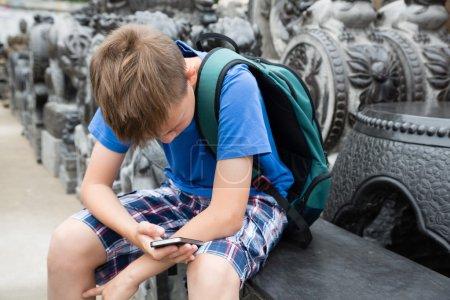 Photo pour Garçon caucasien utilisant un smartphone sur le célèbre Panjiayuan Antique Marke - image libre de droit