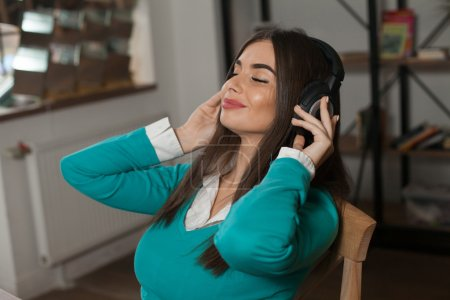 Woman with headphones on chair