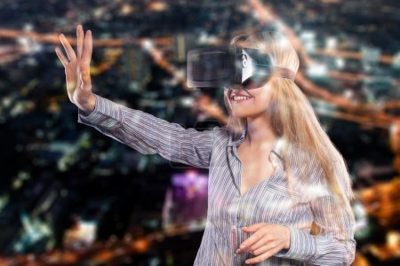 Photo for Pretty woman in grey shirt touching something curiously using the virtual reality headset on black background. - Royalty Free Image