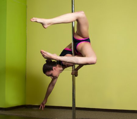 Pole dancer in the pole dance studio