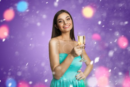 Photo for Smiling young woman with glass of champagne indoors - Royalty Free Image