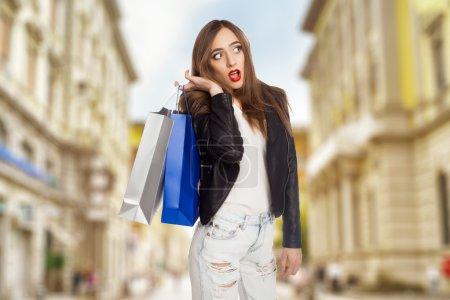 Photo pour Jeune femme debout à l'extérieur avec des sacs à provisions - image libre de droit