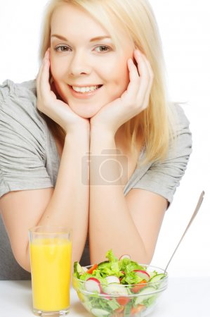 Photo for The beautiful cheerful young woman has breakfast salad from fresh vegetables with orange juice - Royalty Free Image