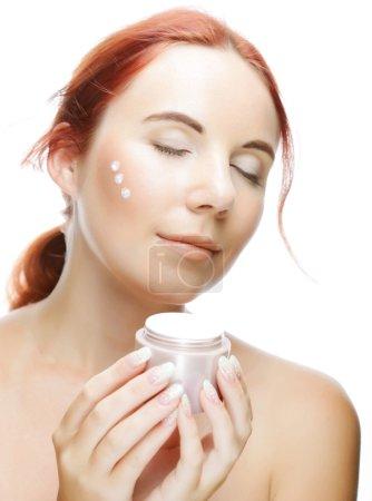 Photo pour Jeune femme souriante appliquant de la crème sur son visage - image libre de droit