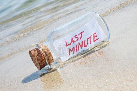 "Message in a vintage bottle ""Last minute"" on beach"