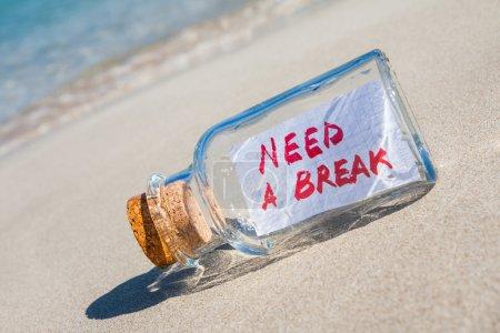 """Photo pour Concept vacances et stress. Bouteille vintage avec message texte """"besoin d'une pause"""" couchée sur une plage de sable - image libre de droit"""