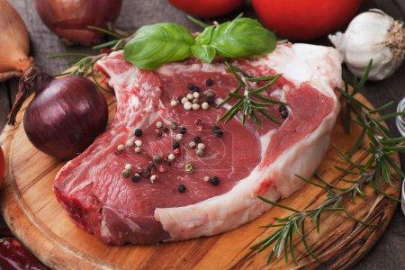 Photo pour Bifteck de côtelette cru sur planche de bois avec maïs poivré et romarin - image libre de droit