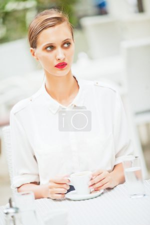 Young beautiful girl drinking coffee