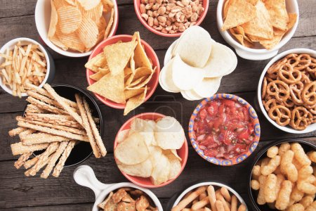 Photo for Salty crackers, tortilla chips and other savoury snacks with salsa dip - Royalty Free Image