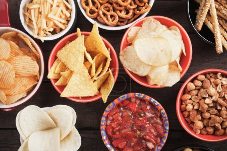 Photo for Tortilla chips and other salty snacks with homemade salsa - Royalty Free Image