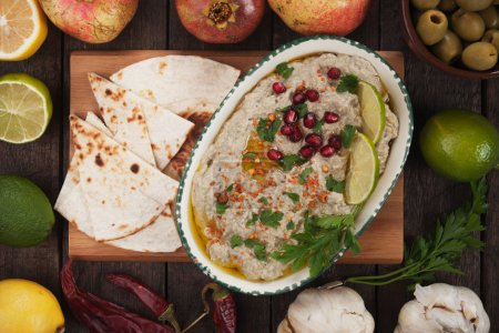 Photo for Baba ghanoush, levantine eggplant dip served with   pita bread, lime slices and pomegranate - Royalty Free Image