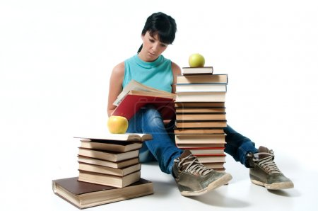 Photo for Young female student sitting and reading,apples on books - Royalty Free Image