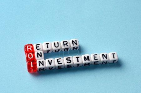 Photo pour ROI Retour sur investissement écrit sur des dés sur fond bleu - image libre de droit