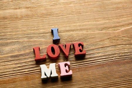 Photo pour J'AIME ME- mot fabriqué à partir de lettres multicolores sur fond en bois couleur chaude - image libre de droit