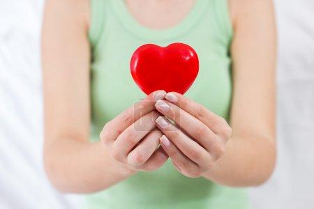 Photo pour Soins de santé amour soutien coeur rouge en mains féminines. - image libre de droit