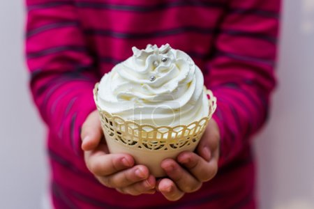 Child hands holding Dessert Muffins.