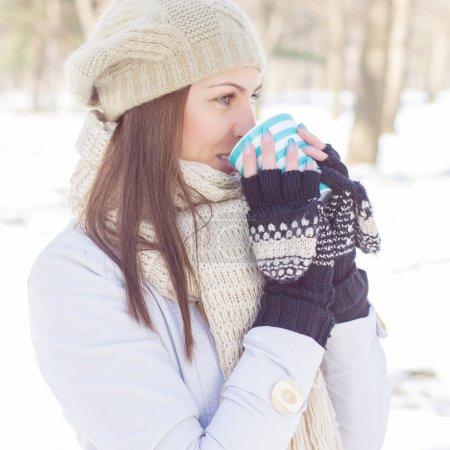 Photo pour Portrait d'hiver d'une belle femme qui aime boire une tasse de thé chaud à l'extérieur.Belle femme relaxante dans le parc . - image libre de droit