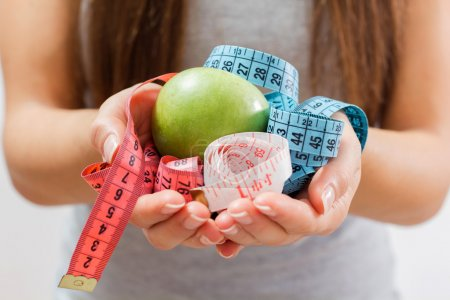 Photo for Green apple and measure tape in woman hand.Diet and weight loss concept. - Royalty Free Image