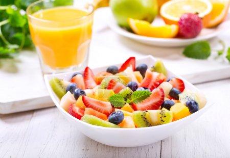 Photo for Bowl of fruit salad on wooden table - Royalty Free Image