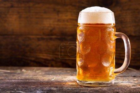 Photo pour Tasse froide de bière sur table en bois - image libre de droit