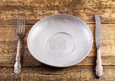 Photo for Empty plate fork and knife on wooden table - Royalty Free Image