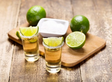 Photo for Glasses of tequila with lime on wooden table - Royalty Free Image