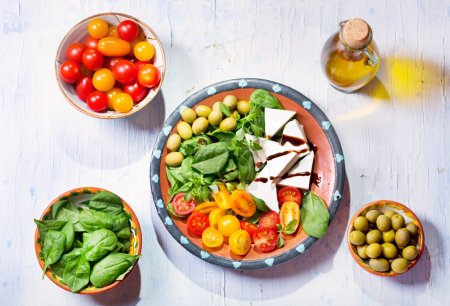 salad with cheese, tomatoes, greens on wooden table, top view