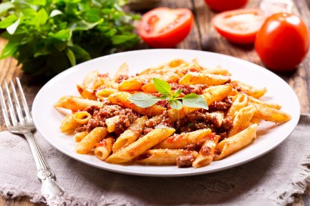 Photo for Plate of pasta bolognese on wooden table - Royalty Free Image