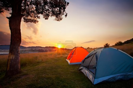 Photo for Recreation area and camp with tent, sunset time with rising sun near hign mountain lake - Royalty Free Image