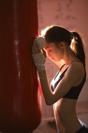 Photo pour Belle fille en gants de boxe pour sac de boxe kick - image libre de droit