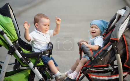 Boy and girl sitting in baby carriages