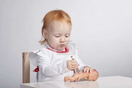 girl playing doctor with a doll