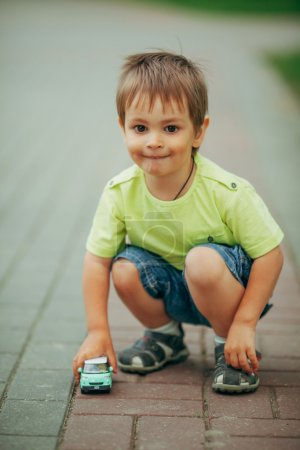 little boy playing with toy car