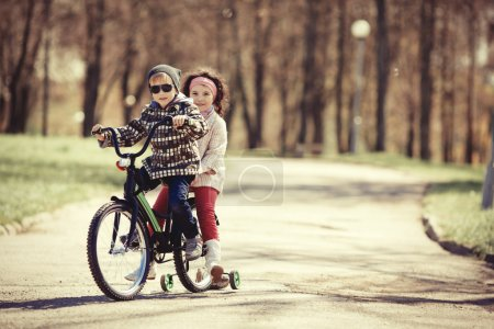 little girl and boy riding on bicycle together
