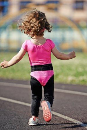 ittle cute girl running at stadium