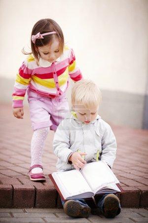 Photo pour Mignon garçon et fille lecture un livre - image libre de droit