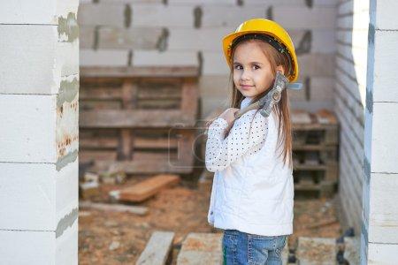 Photo pour Petite fille mignonne avec casque travaillant sur la construction - image libre de droit