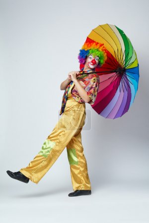 Clown with colorful umbrella on white