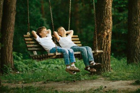 Foto de Foto de dos chicos soñando en columpio - Imagen libre de derechos