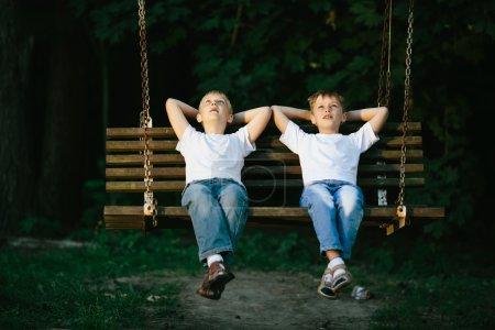 Photo pour Photo de deux petits garçons rêvant sur balançoire - image libre de droit