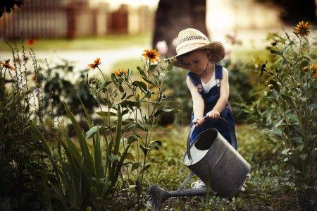 Photo pour Mignon petit garçon avec arrosoir dans le parc d'été - image libre de droit