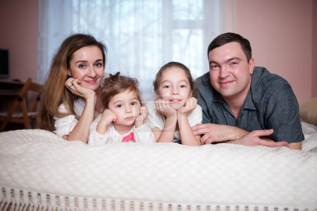 Photo for Happy young family lying in bed at home - Royalty Free Image