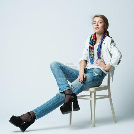 Photo pour Belle fille avec les cheveux longs posant sur la chaise - image libre de droit