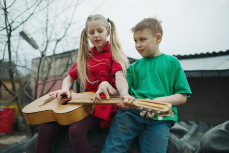 Photo pour Enfants heureux apprennent à jouer de la guitare - image libre de droit